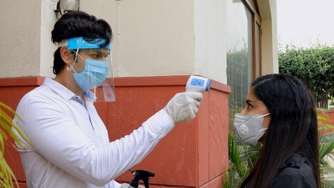 Worker checking the temperature of a female customer wearing a medical mask - Corona / Covid
