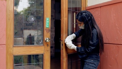 Female worker sanitizing the door handles while wearing a mask and rubber gloves
