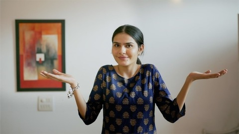 A confused girl in traditional wear spreading her hands in a questioning gesture