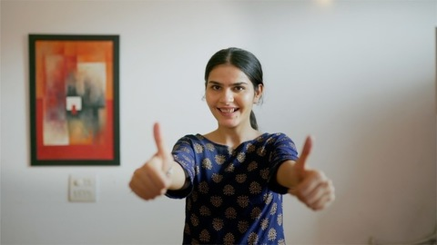 Pretty Indian girl showing double thumbs-ups while smiling towards the camera