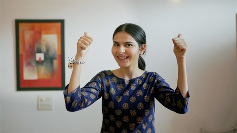 Pretty Indian female happily gesturing thumbs-ups while standing against a wall