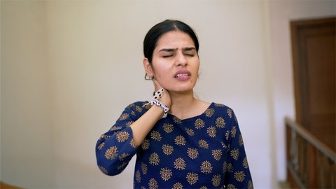 An attractive young girl suffering from severe neck pain - health/medical concept
