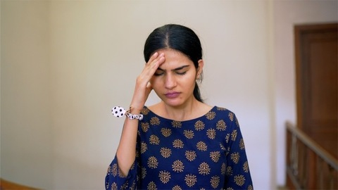 Pretty Indian girl suffering from a severe headache - health and medical concept
