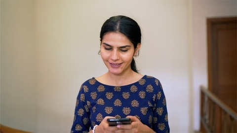 Pretty Indian female calling someone from her smartphone - traditional wear