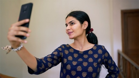 Portrait of a beautiful young female happily taking selfies in trendy traditional Kurti