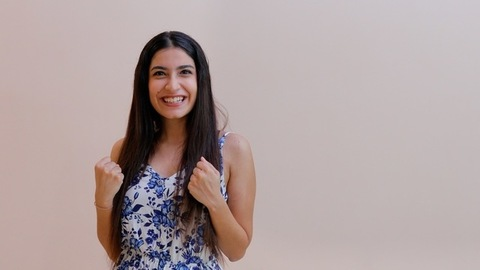 Excited Indian female happily doing winning gesture against a wall background