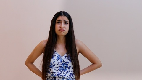Young girl showing negative emotions while standing against a wall background
