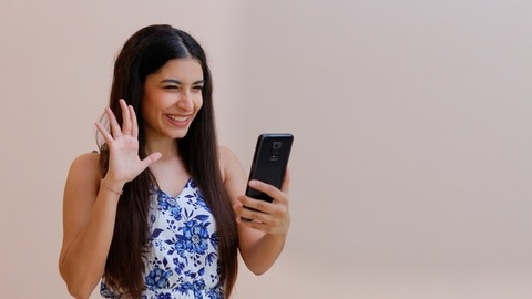 Portrait shot of a beautiful young female happily doing video call to her friends