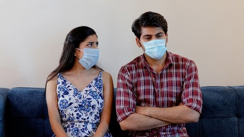 Young boyfriend girlfriend using protective medical masks while sitting at home