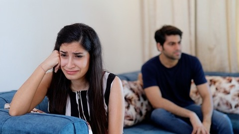 Frustrated Indian man yelling and shouting at his girlfriend while she is crying