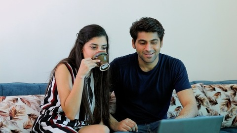 An adorable and young husband-wife happily spending quality time together at home