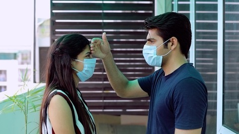 Caring Indian husband touching his wife's forehead to check her body temperature