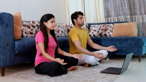Young boyfriend girlfriend learning breathing exercises in an online yoga class