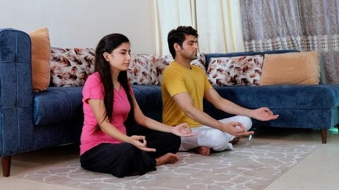 Young boyfriend girlfriend doing rhythmic breathing exercises in the living room