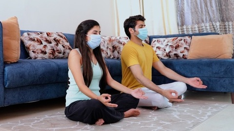 Young boyfriend girlfriend meditating in Sukhasana (easy pose) for a healthy lifestyle