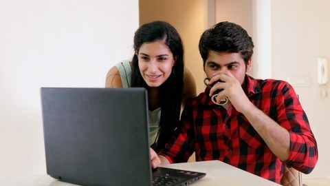 Young and newly married happy Indian couple working on the laptop