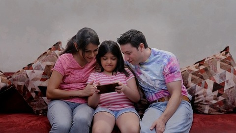 A little girl playing a game on a smartphone and the parents sitting by her side