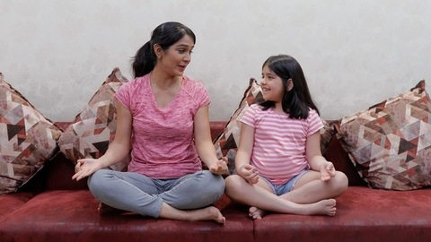 Long shot of a mother-daughter exercising together while talking to each other