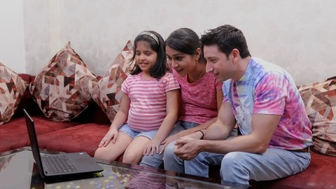 An Indian modern family of three using a laptop to make a video call to the relatives