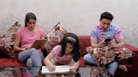 A little child doing her homework while the parents are busy on smart gadgets