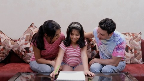 A young Indian dad and mom supporting their little girl while she studies in a proper way
