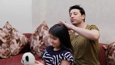A caring father combing his daughter's hair while she plays with her toy