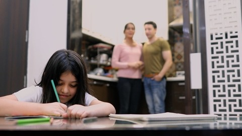Long shot of parents watching their kid study happily inside their home