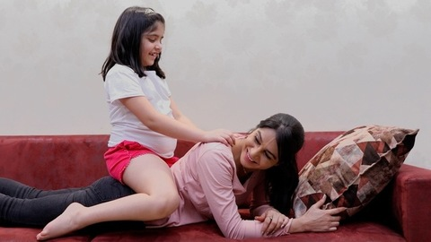 A mother-daughter duo enjoying each other's company playfully at their home