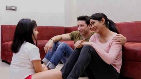 A young married couple chatting with their daughter in the living room