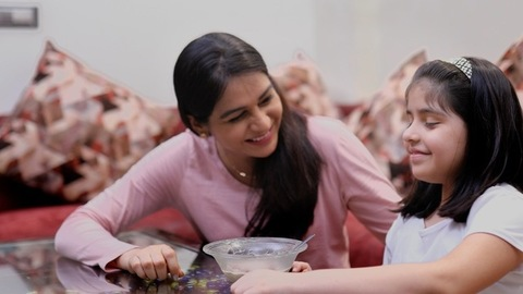 A medium shot of a mother-daughter sharing the tasty food from a bowl