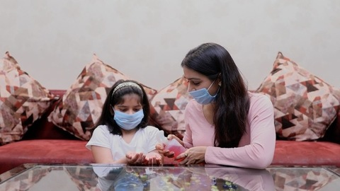 A mother-daughter sanitizing their hands to prevent the spread of the virus