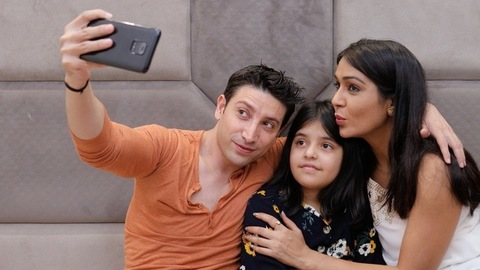 Medium shot of a young couple with their child clicking a selfie using a smartphone