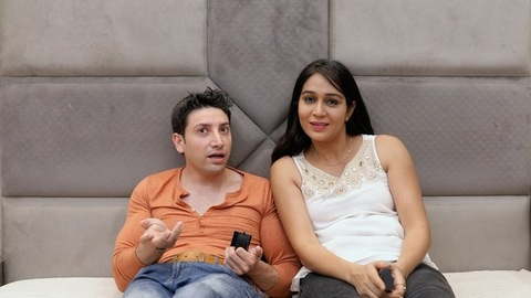 An attractive Indian couple fighting over the choice of television channels