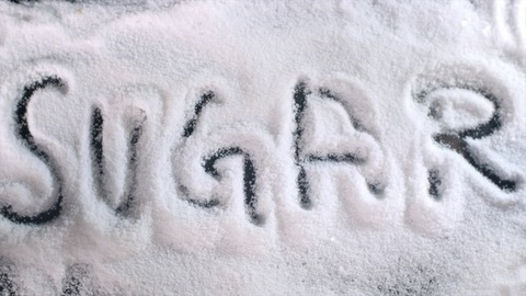 """Human / female hands writing the word """"SUGAR"""" with the help of letters and alphabets"""