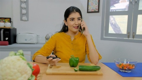 A pretty Indian lady busy talking on her smartphone with a friend in the kitchen
