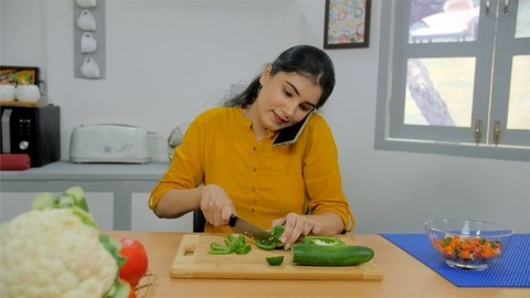 A lovely woman involved in talking with her friends while chopping fresh vegetables