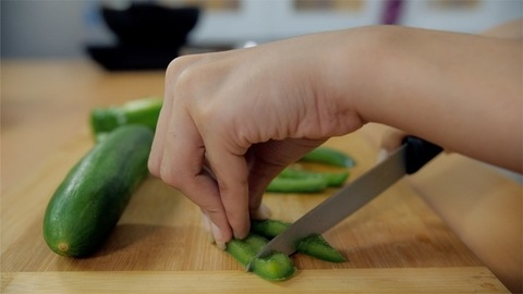 Close up shot of a woman's hand-chopping green capsicum to prepare a salad