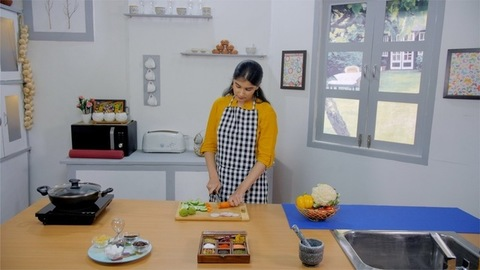A beautiful girl cutting fresh vegetables to prepare healthy food in her kitchen