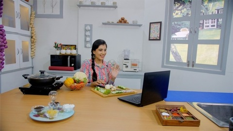 A young lady making a video call while sitting and chopping veggies in a kitchen