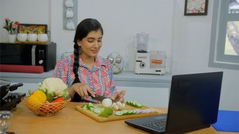 An Indian girl busy replying to a message while cutting vegetables in the kitchen