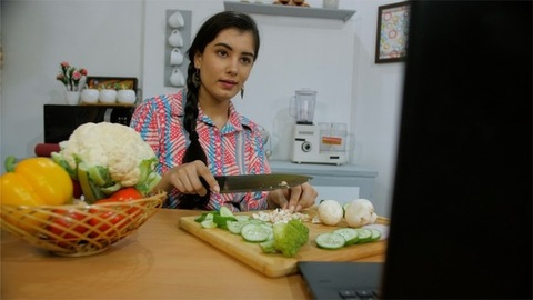 A beautiful girl cutting fresh vegetables bought from the market in her kitchen
