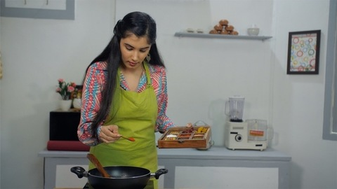A beautiful girl adding spices in the dish from a wooden spice-box while cooking