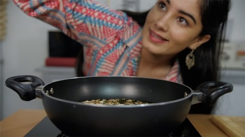 Close up shot of a young girl seasoning the hot and tasty food kept in the pan