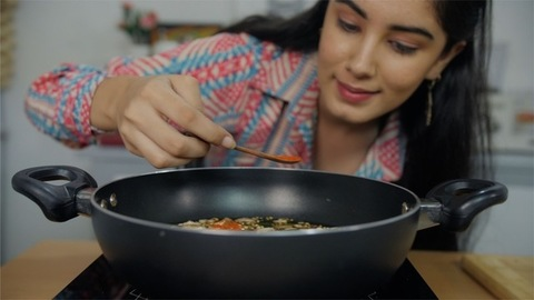 Close up shot of a girl putting some red chili powder in the food made by her