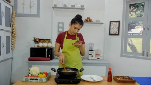 A happy Indian woman chatting on a smartphone while cooking inside her kitchen