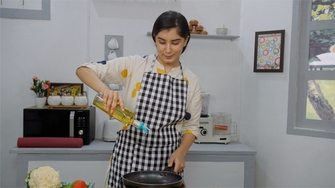 A pretty woman wearing an apron puts effort to open an oil container while cooking
