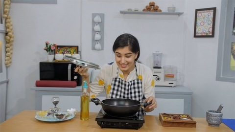 A young Indian woman with a happy face smells the food made by her in a kitchen