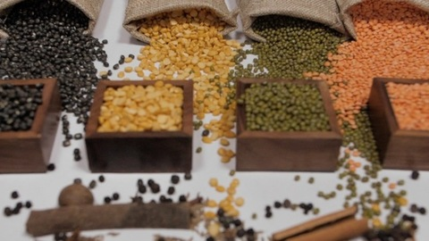 Raw pulses falling from gunny bag in front of wooden containers with Dal/lentils