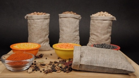 Gunny bag/jute sack full of dried whole spices falling on a wooden table with lentils