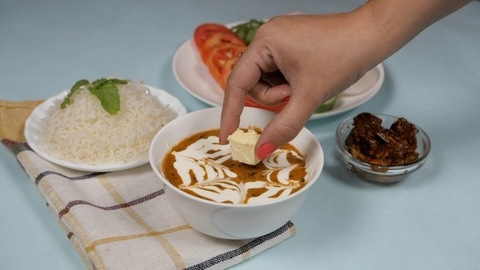Famous Indian meal of steamed rice and dal makhani served with salad and pickle
